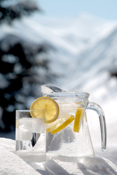 clean water in a pitcher with lemons, sitting in snow